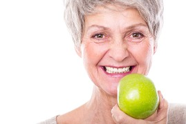 Older woman with a dental implant holding an apple.