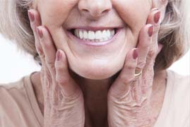 older woman holding her face and smiling