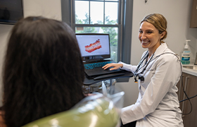 A person pointing to their teeth with a magnifying glass held up in front of their mouth