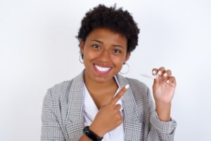 woman holding clear aligners smiling